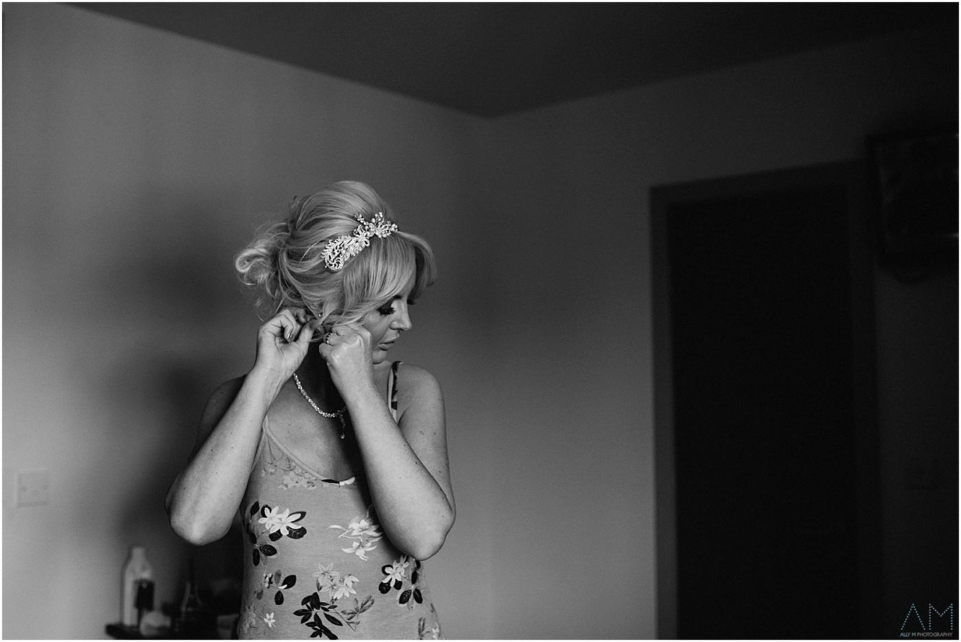 bride putting earings in