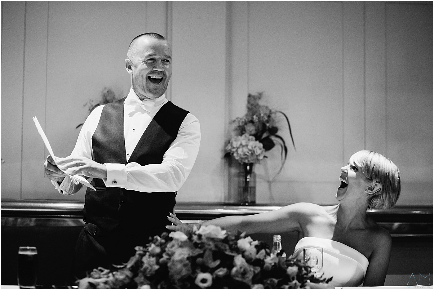 Groom and his bride laughing during speeches