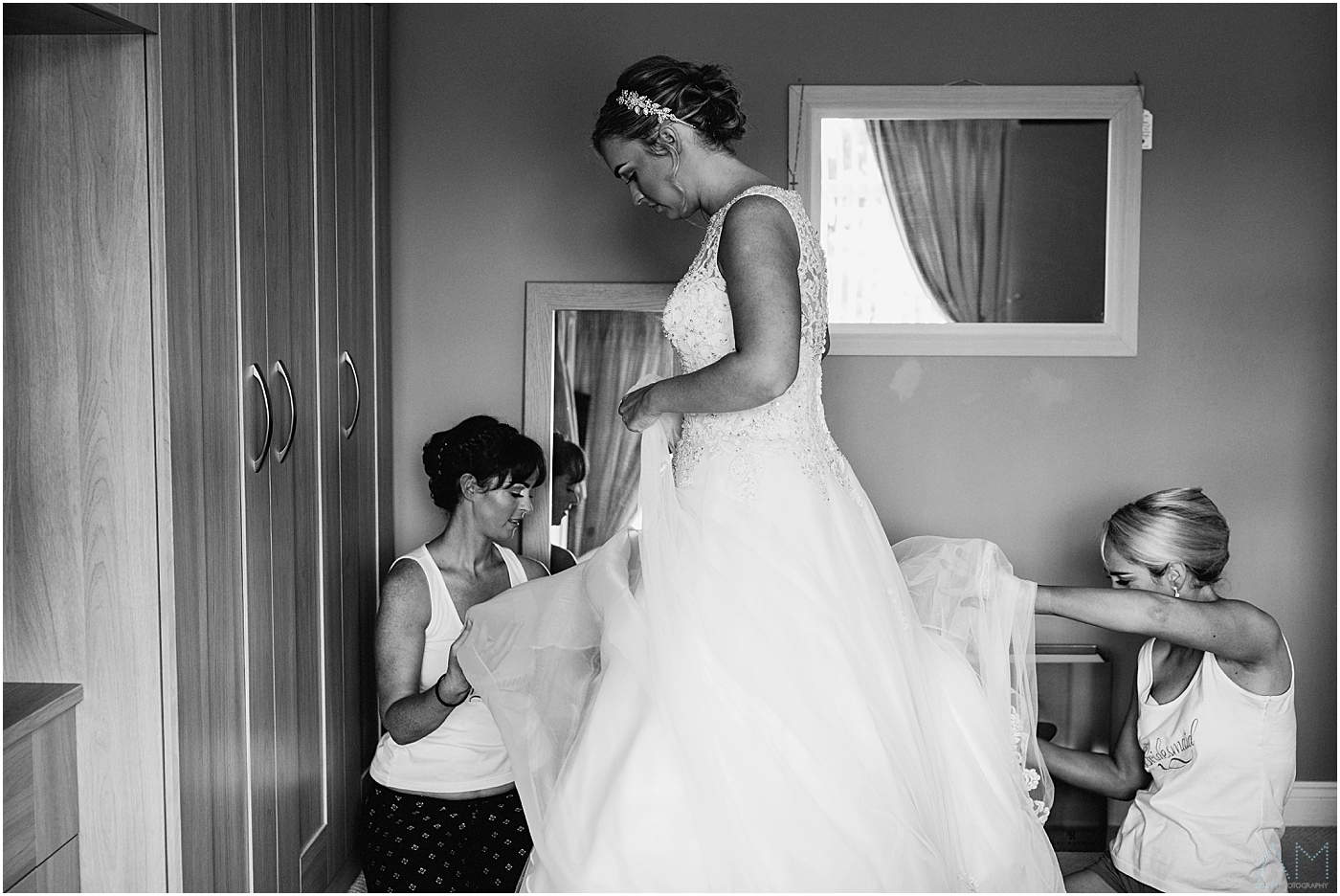 Bride getting helped into her dress by her sister
