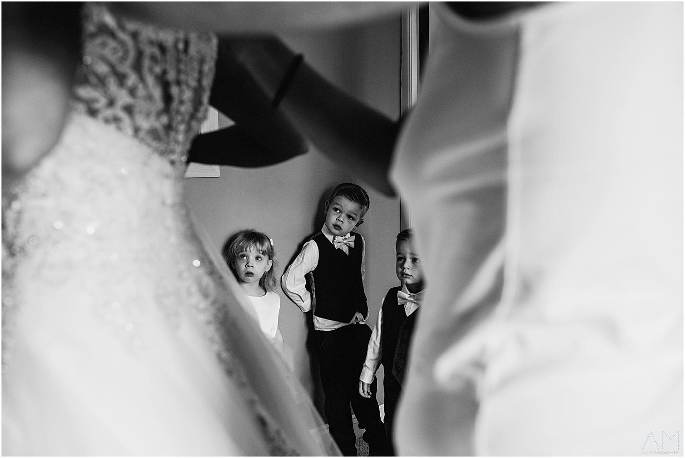 Children watching bride get into her wedding dress