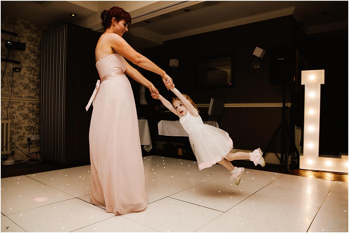 Bridesmaid swinging her daughter on danc floor