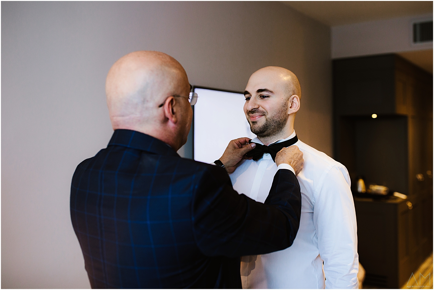 groom having bow tie fastened