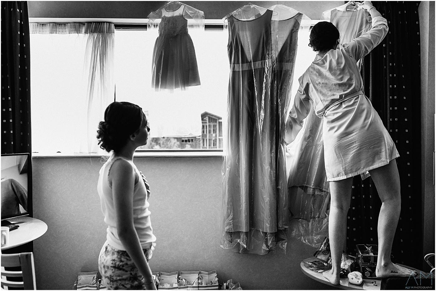 brides sister hanging up dresses
