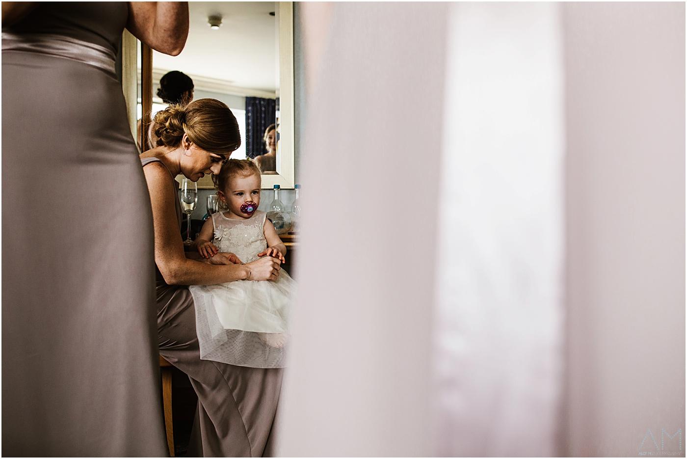 Little girl sat on bridesmaids knee