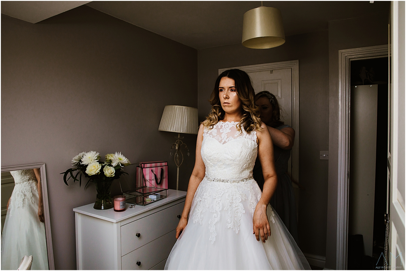 Bride getting help with her wedding dress