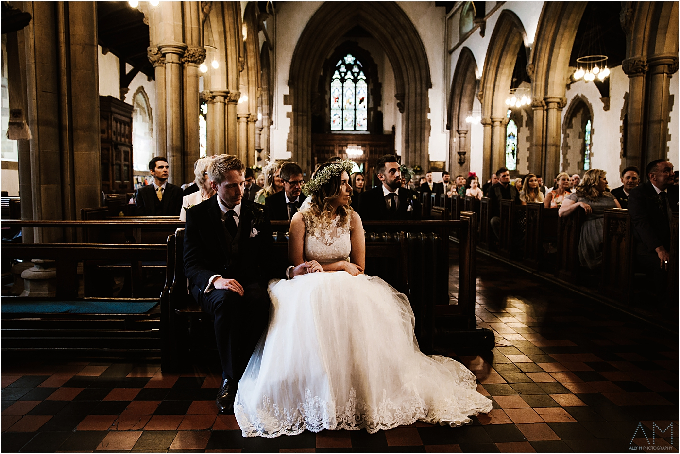 Bride and groom sat together at church in Manchester