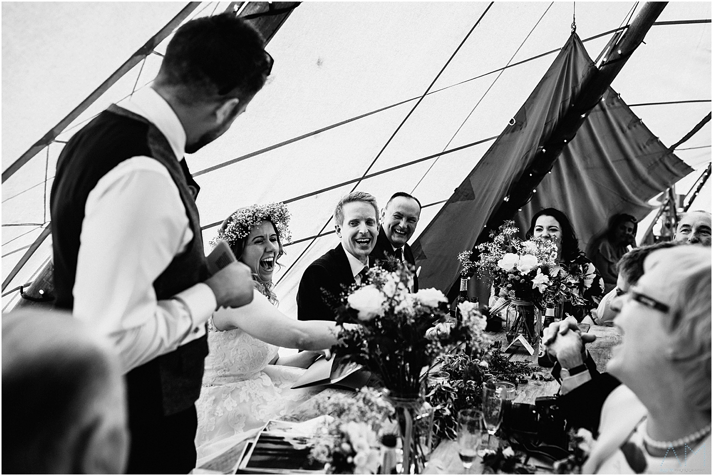 Laughing wedding party during best man speech