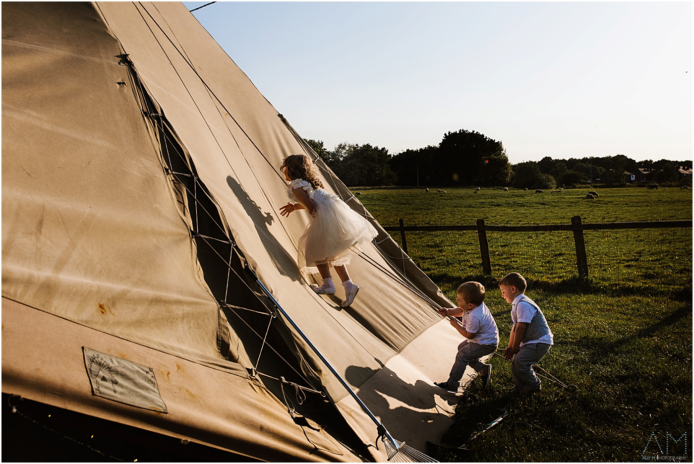 Children climbing up the wedding teepee