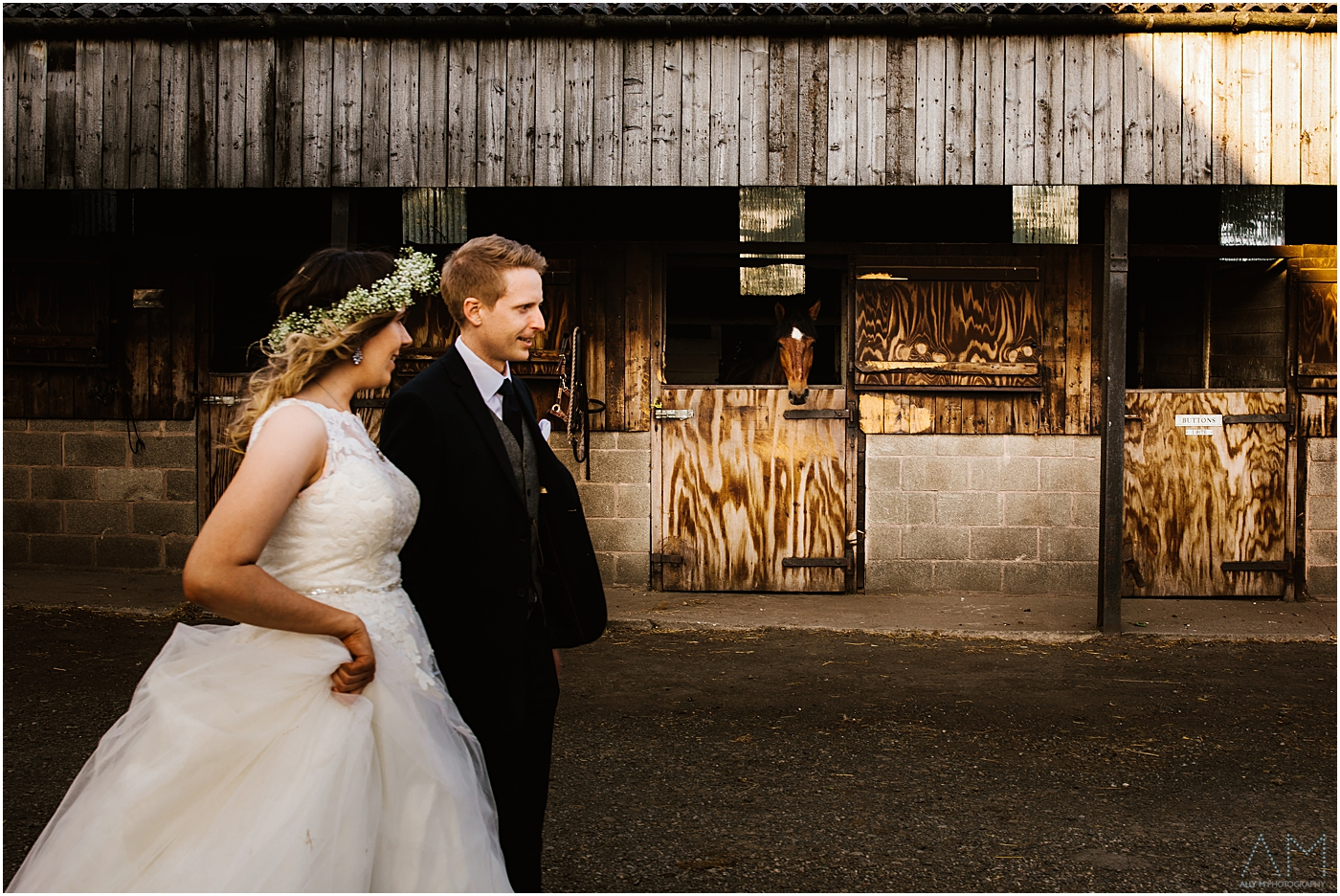 Bride and groom walking past a horse