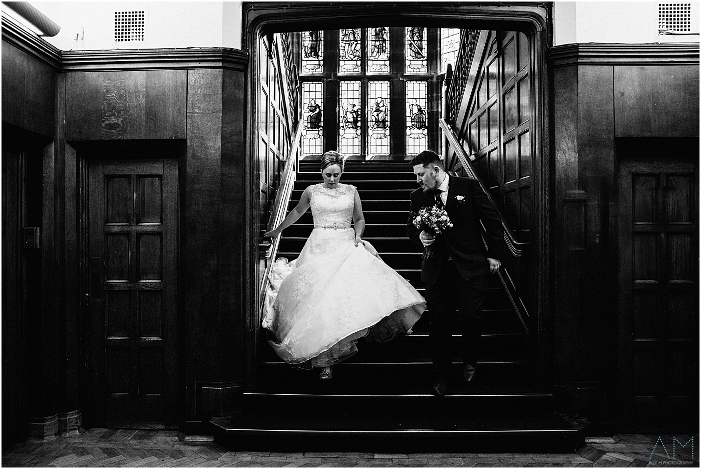 Bride and groom walking down the steps in the great hall