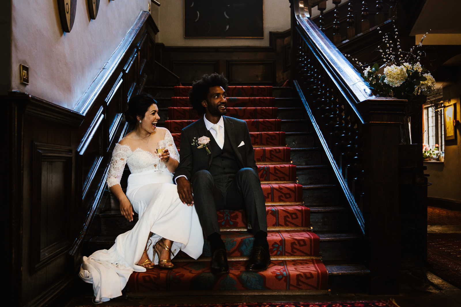 Bride and groom sat on the stairs at Askham Hall