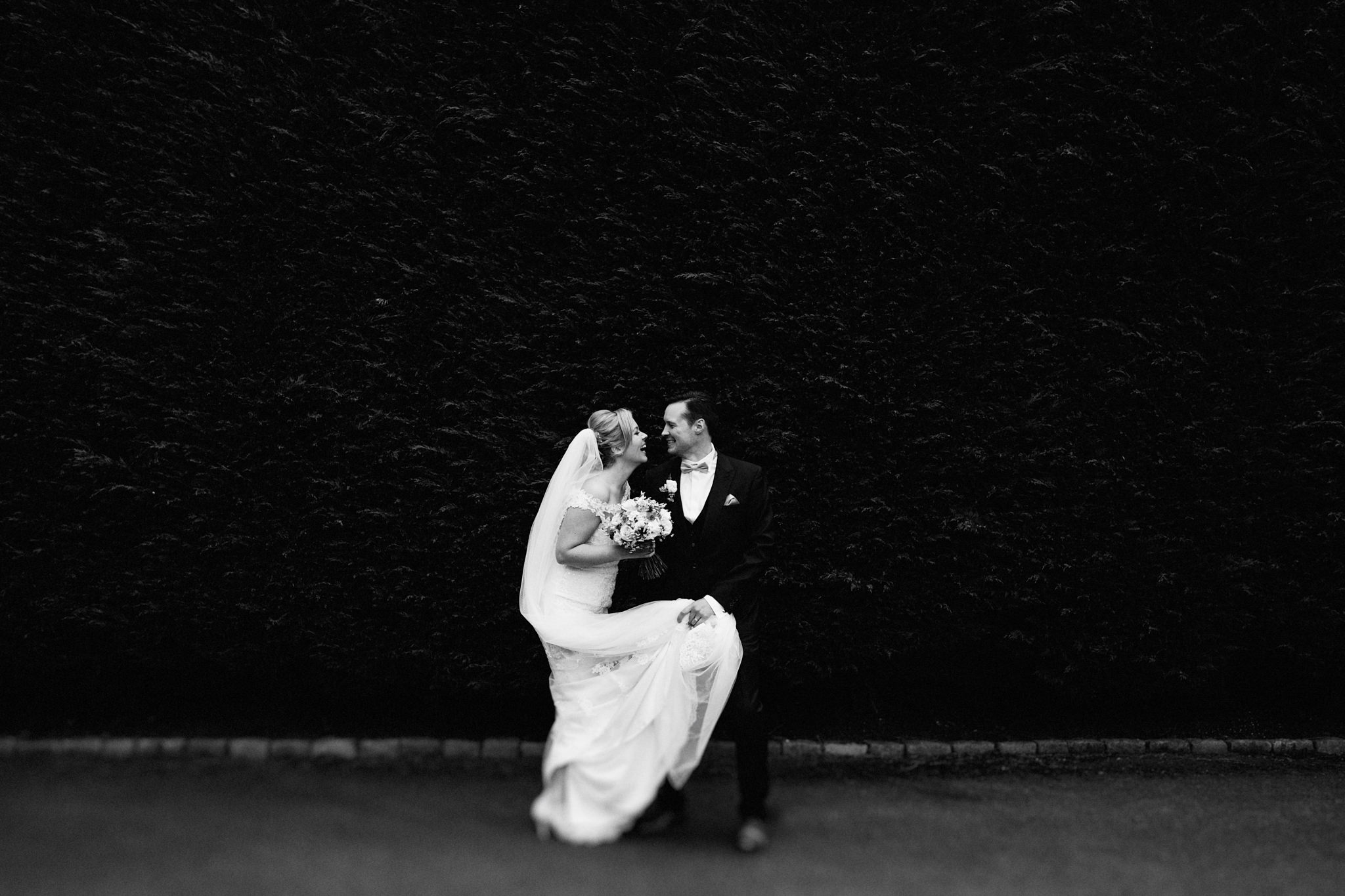 Black ans white portrait of bride and groom laughing