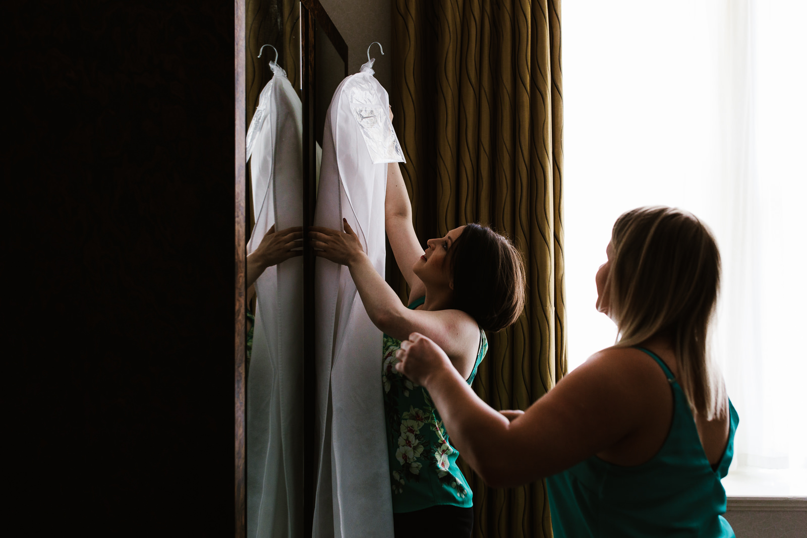 Bride getting down her wedding dress.