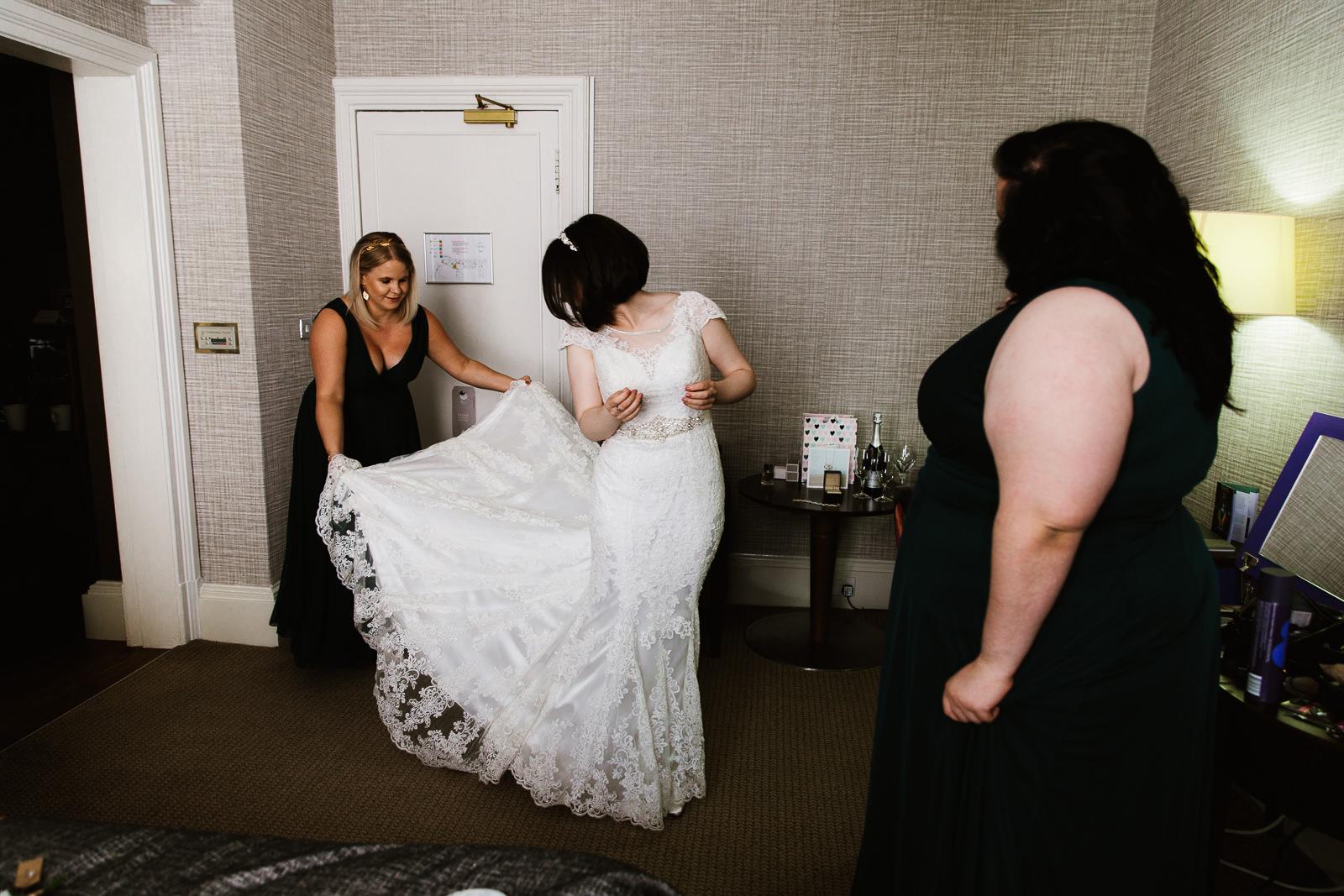 Bridesmaid holding wedding dress.