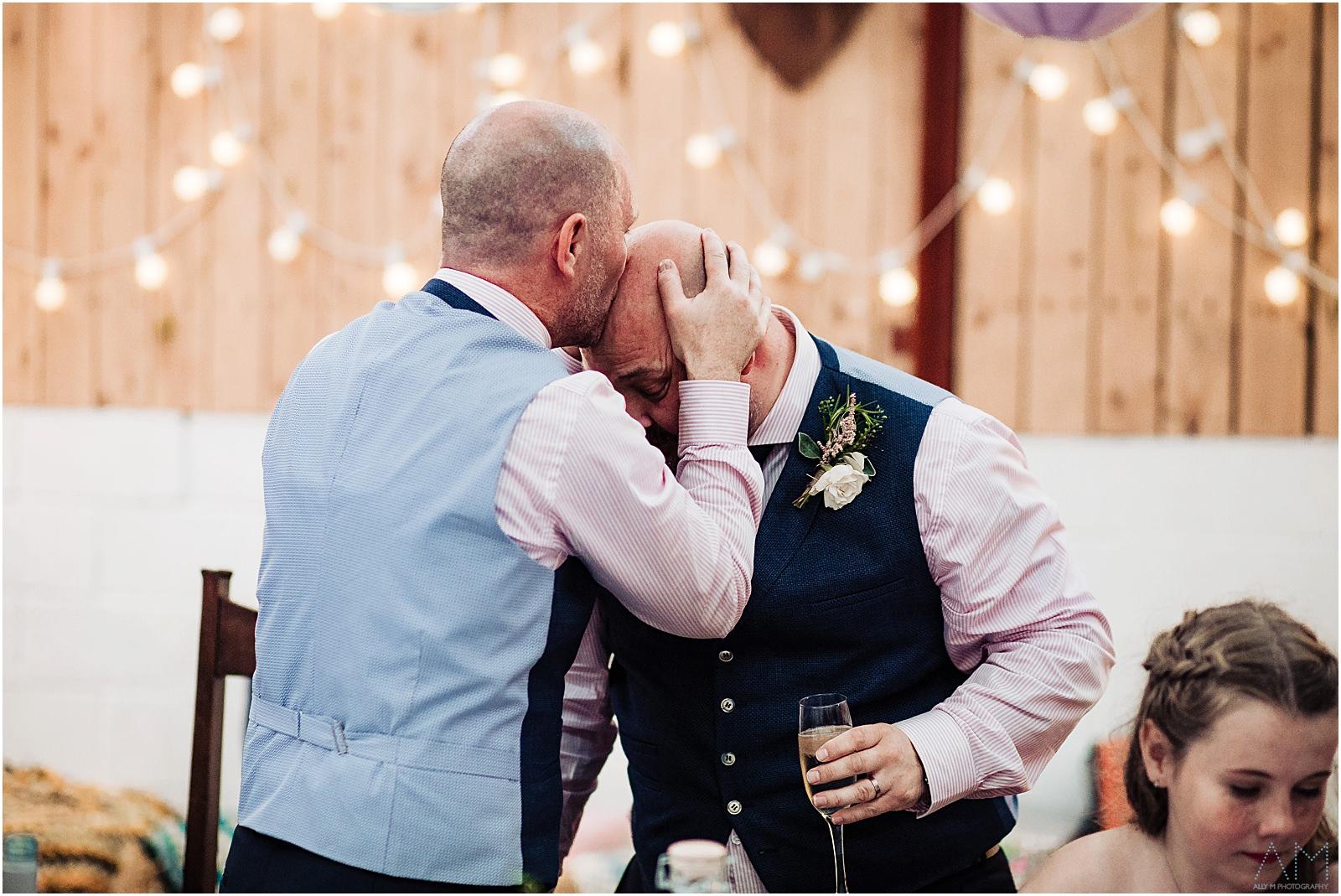 Groom kissing best man on the head