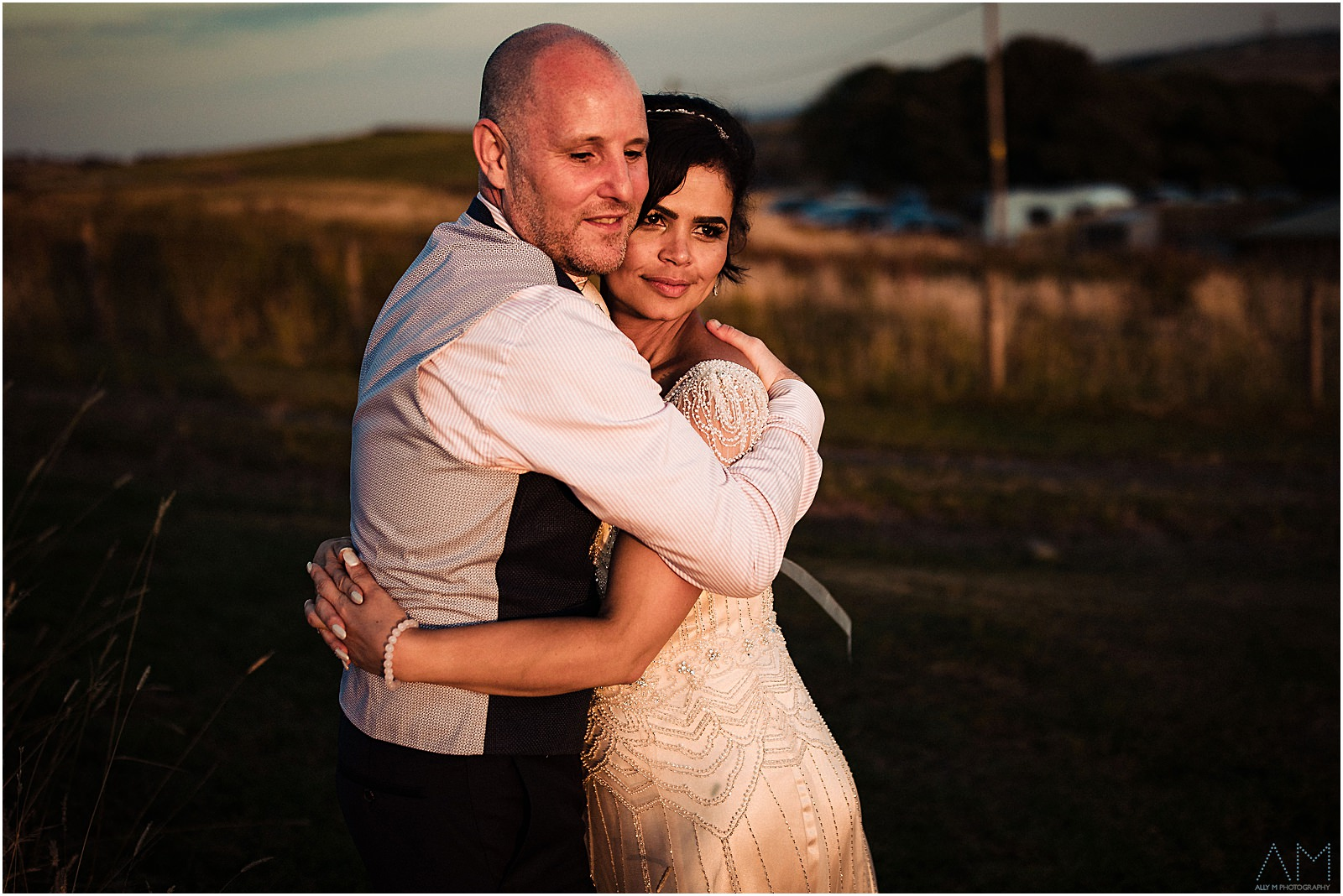 Bride and groom holding each other during sunset
