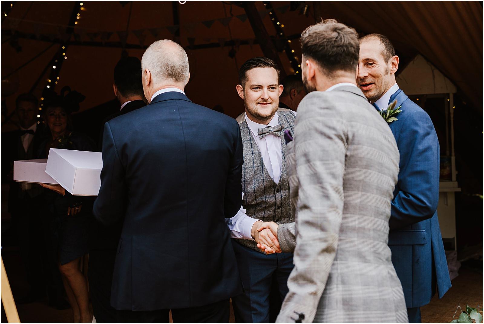 Groom greeting wedding guests