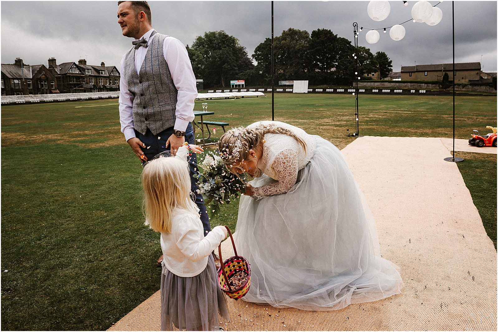 Girl throws confetti on bride