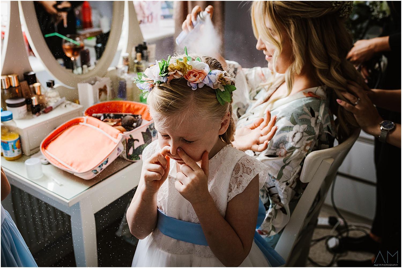 Little girl holding her nose.