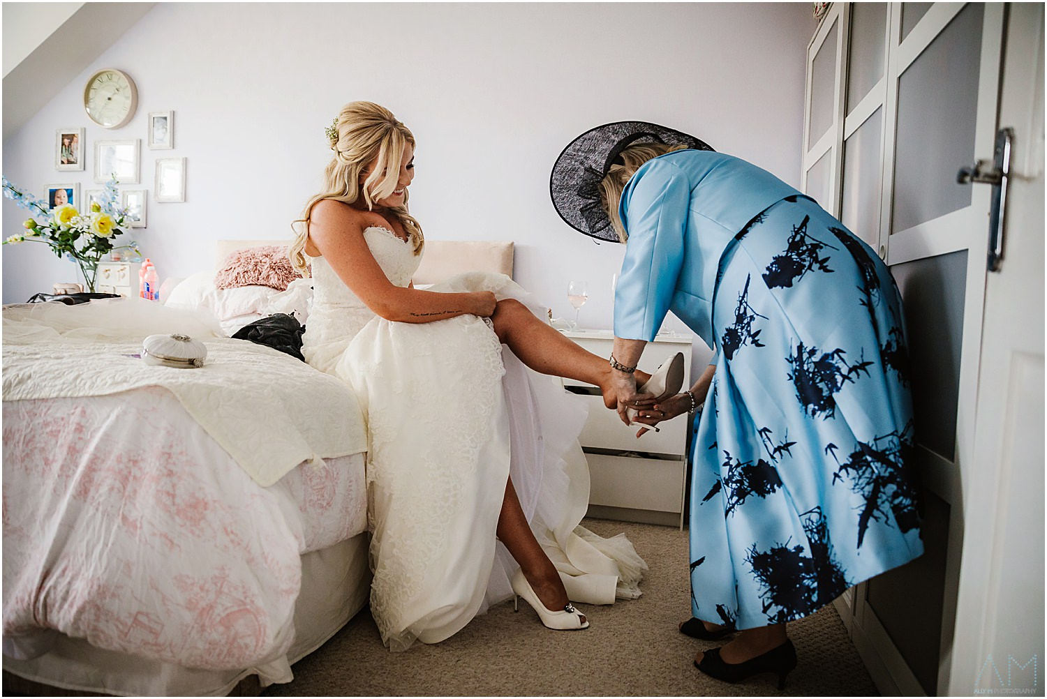 Mother of the bride helping with wedding shoes
