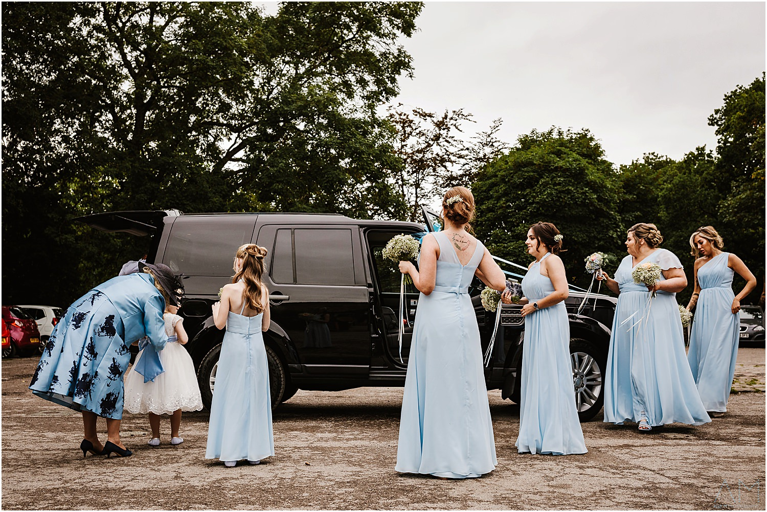 Bridesmaids standing around the car