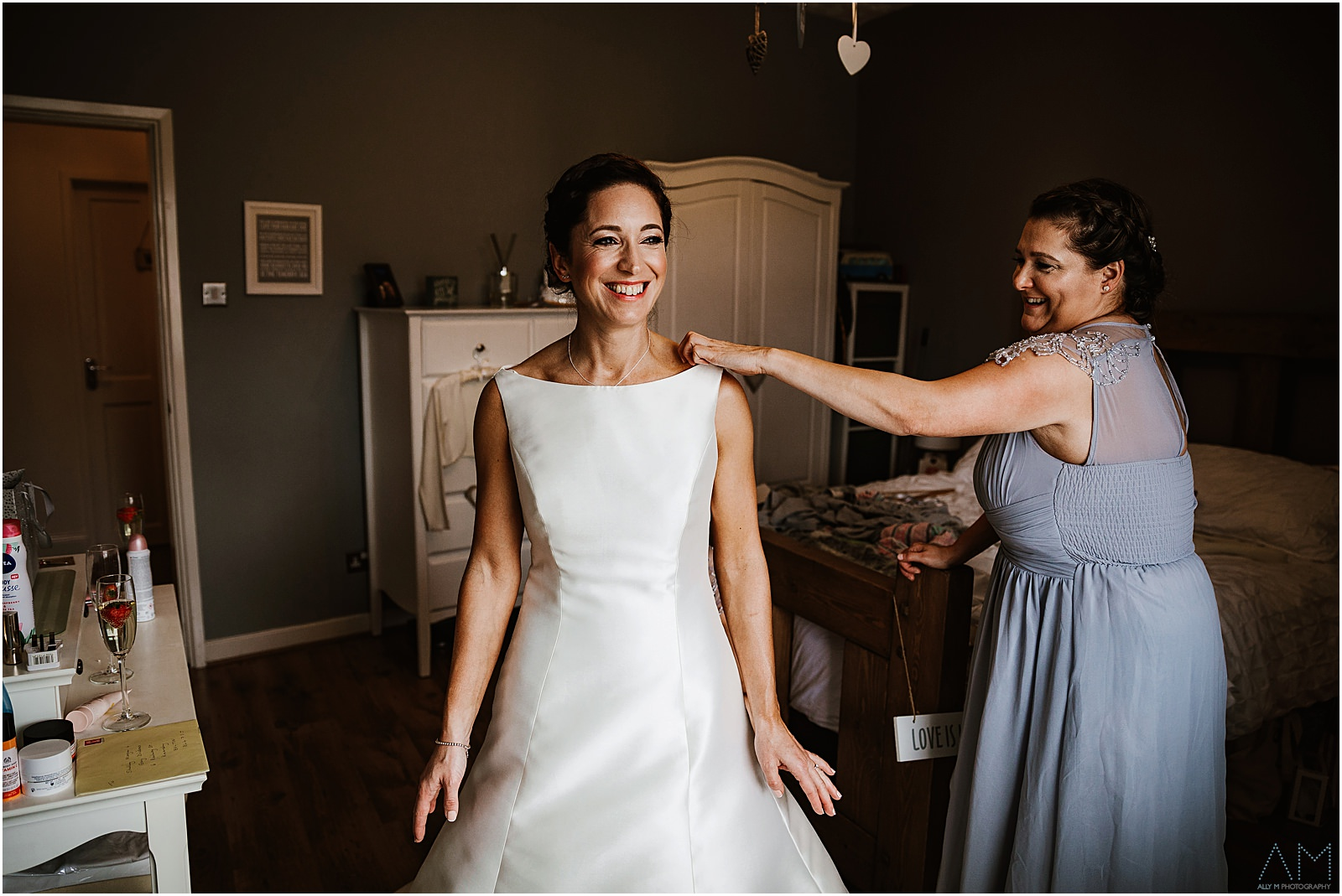 Bridesmaid helping the bride into her wedding dress