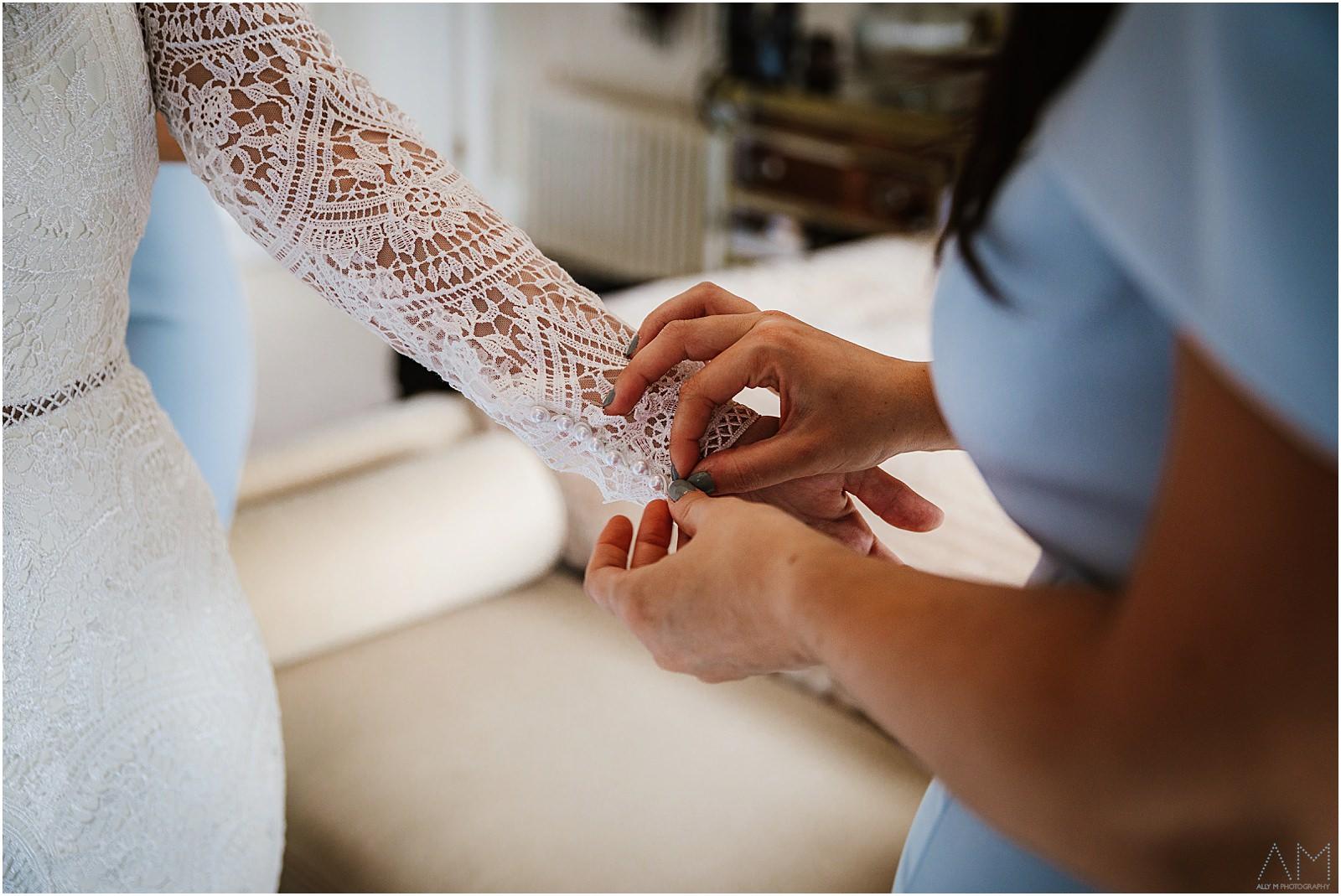 Bridesmaid helping bride with sleeve