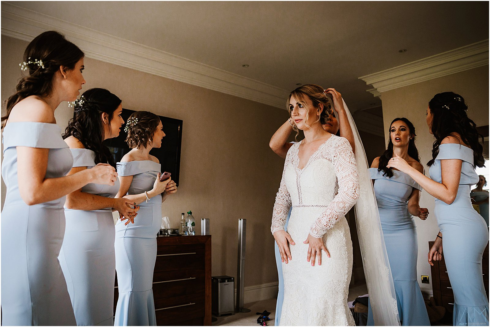 Bride getting help with her wedding dress from the bridesmaids