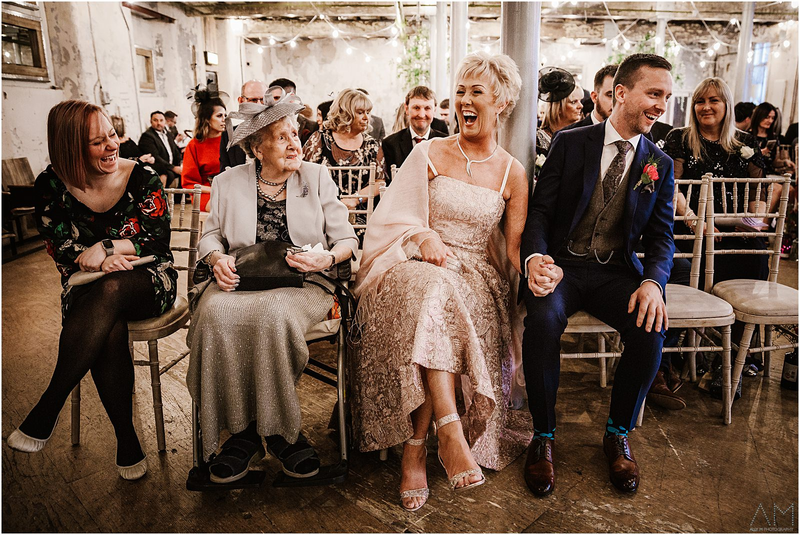 Wedding party laughing together at Holmes Mill