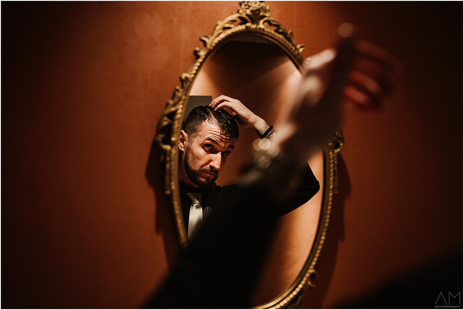 Groom doing his hair in the mirror