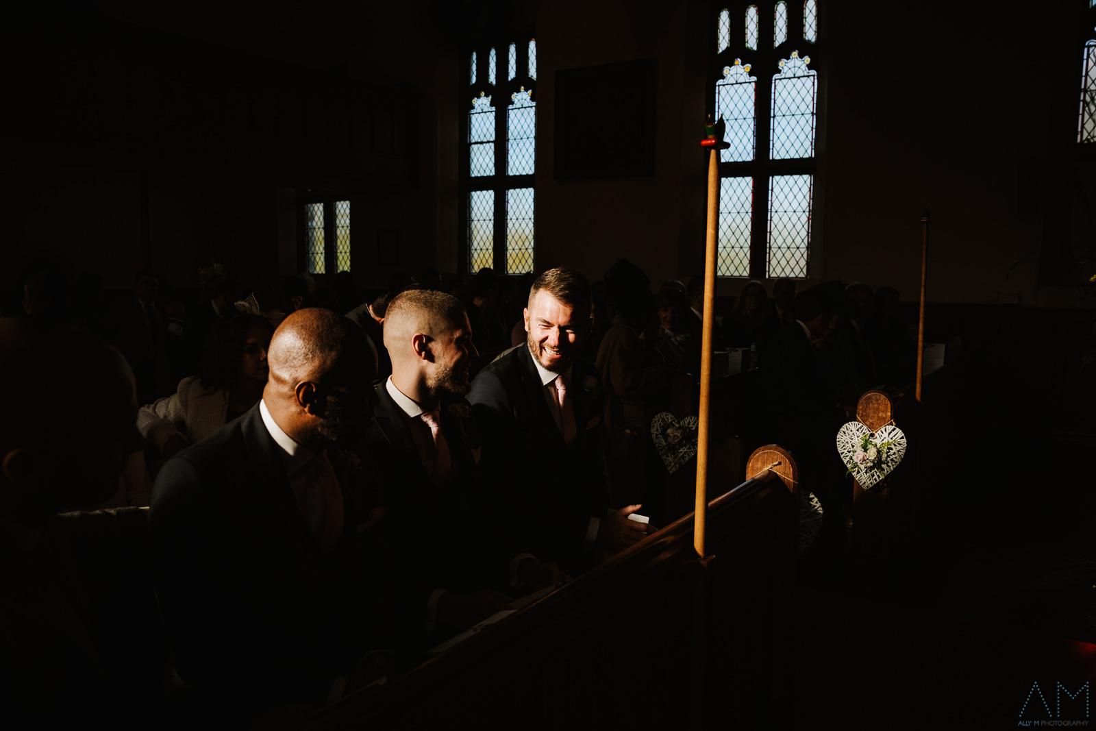 Groom sat in lovely light in church