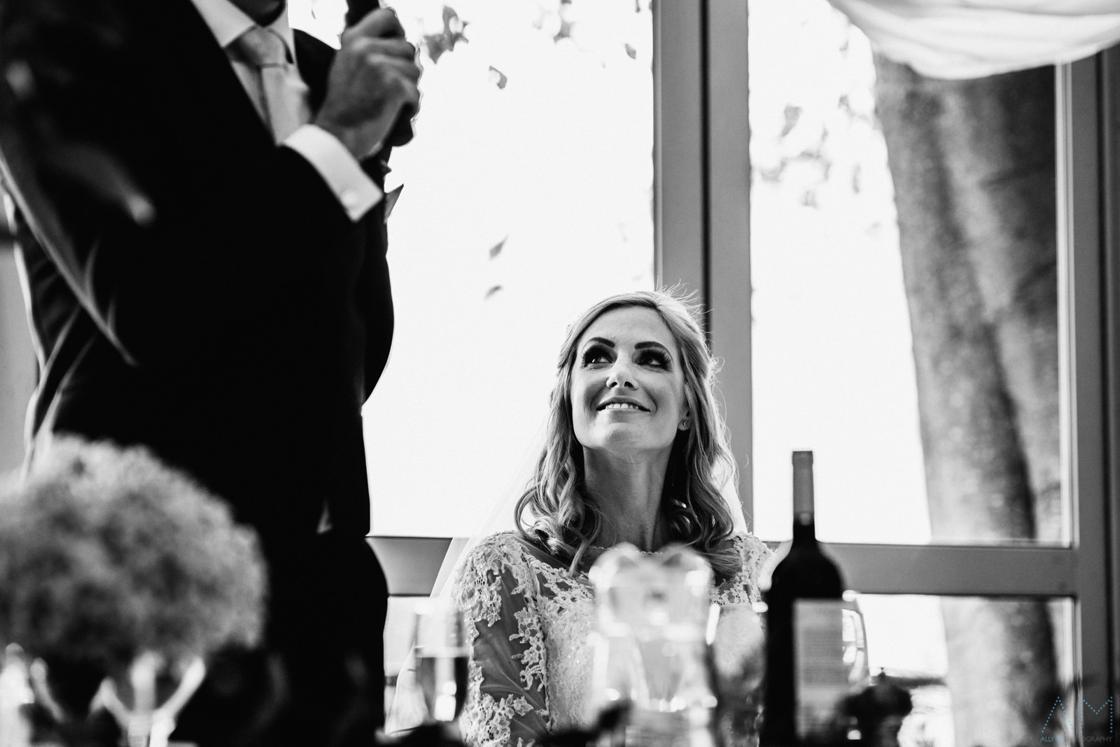 Bride smiling during groom speech