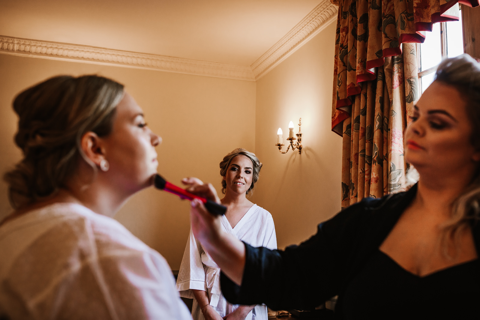 Bride watching her bridesmaid having her make up applied