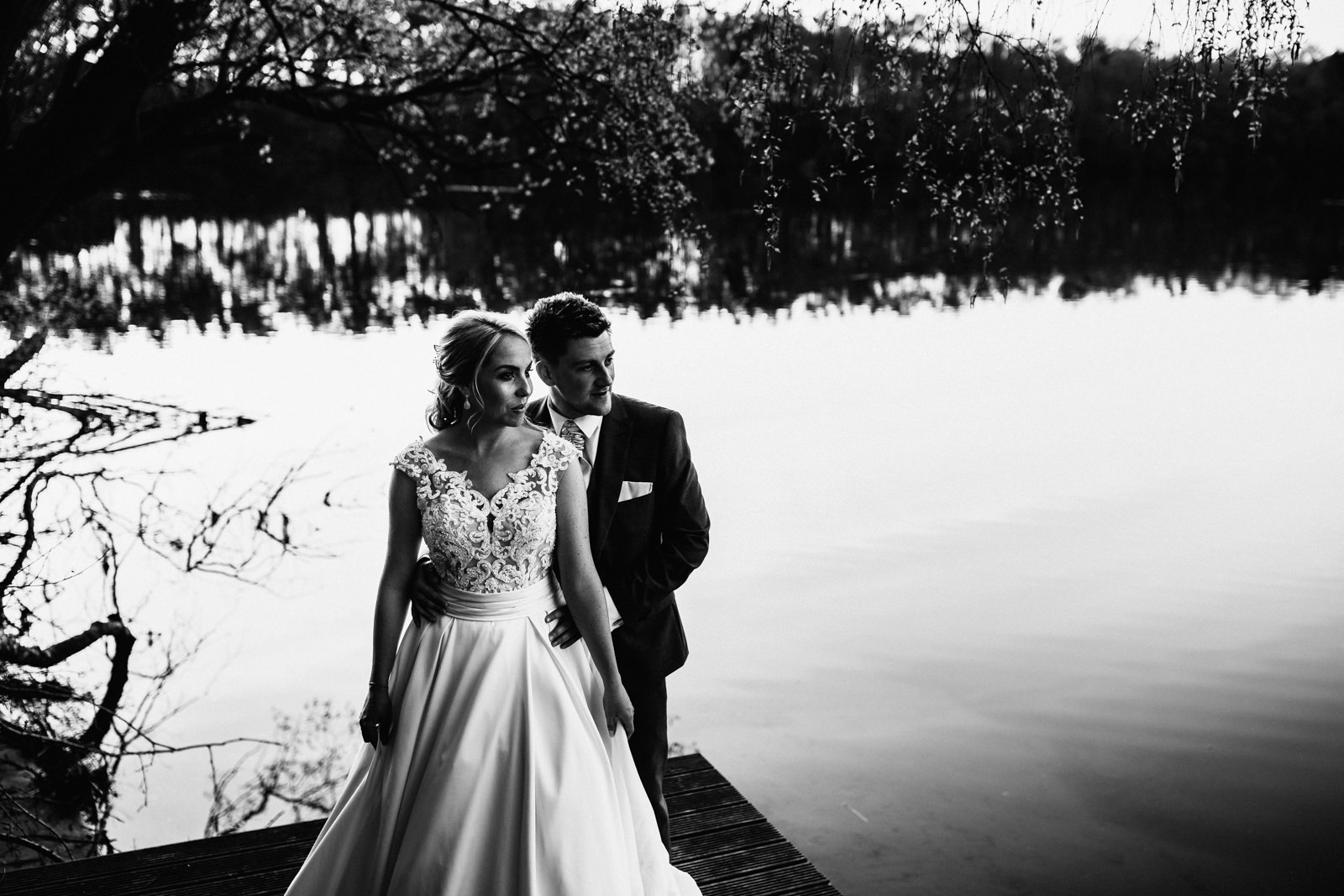 Bride and groom stood by the lake
