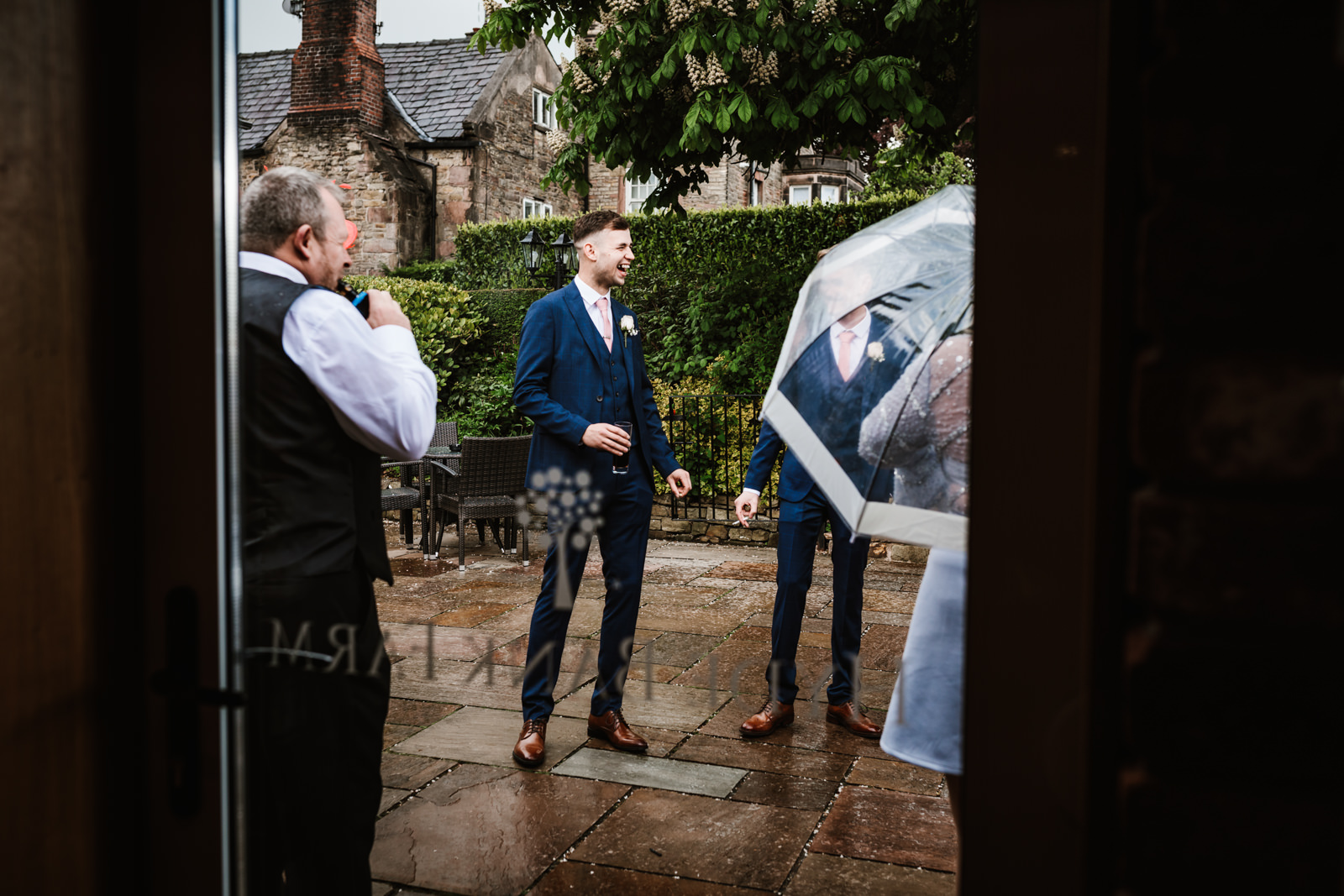 Groom with his guests in the rain
