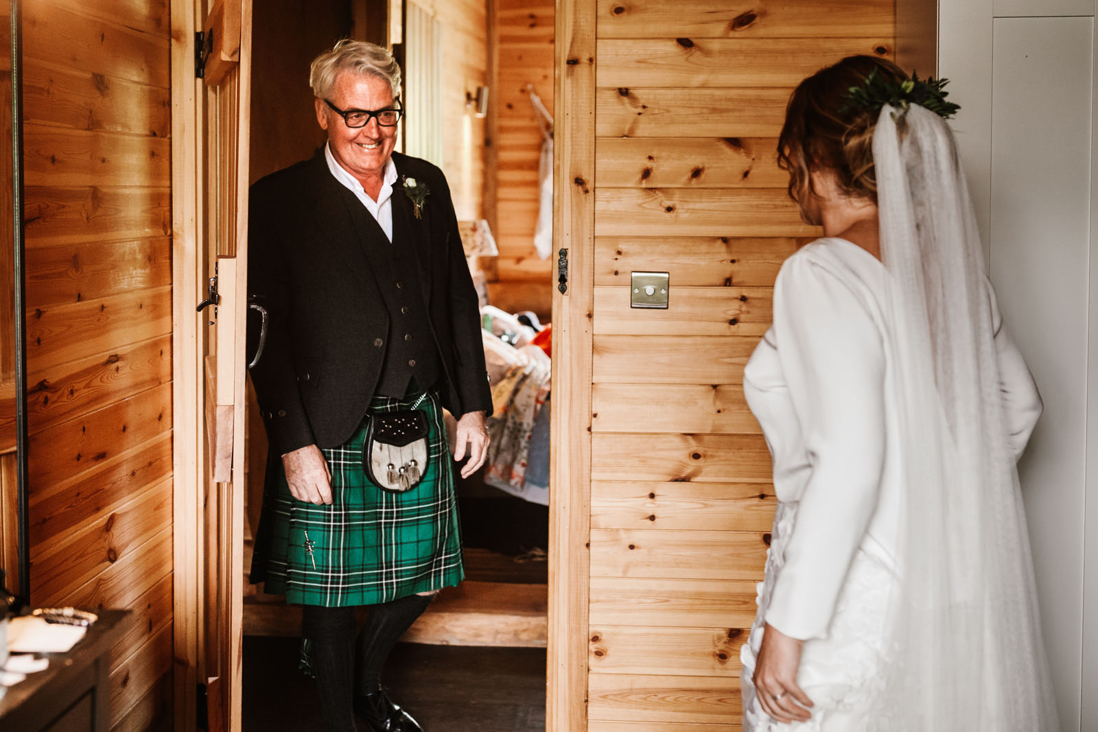 Father of the bride looks at his daughter for the first time in her wedding dress