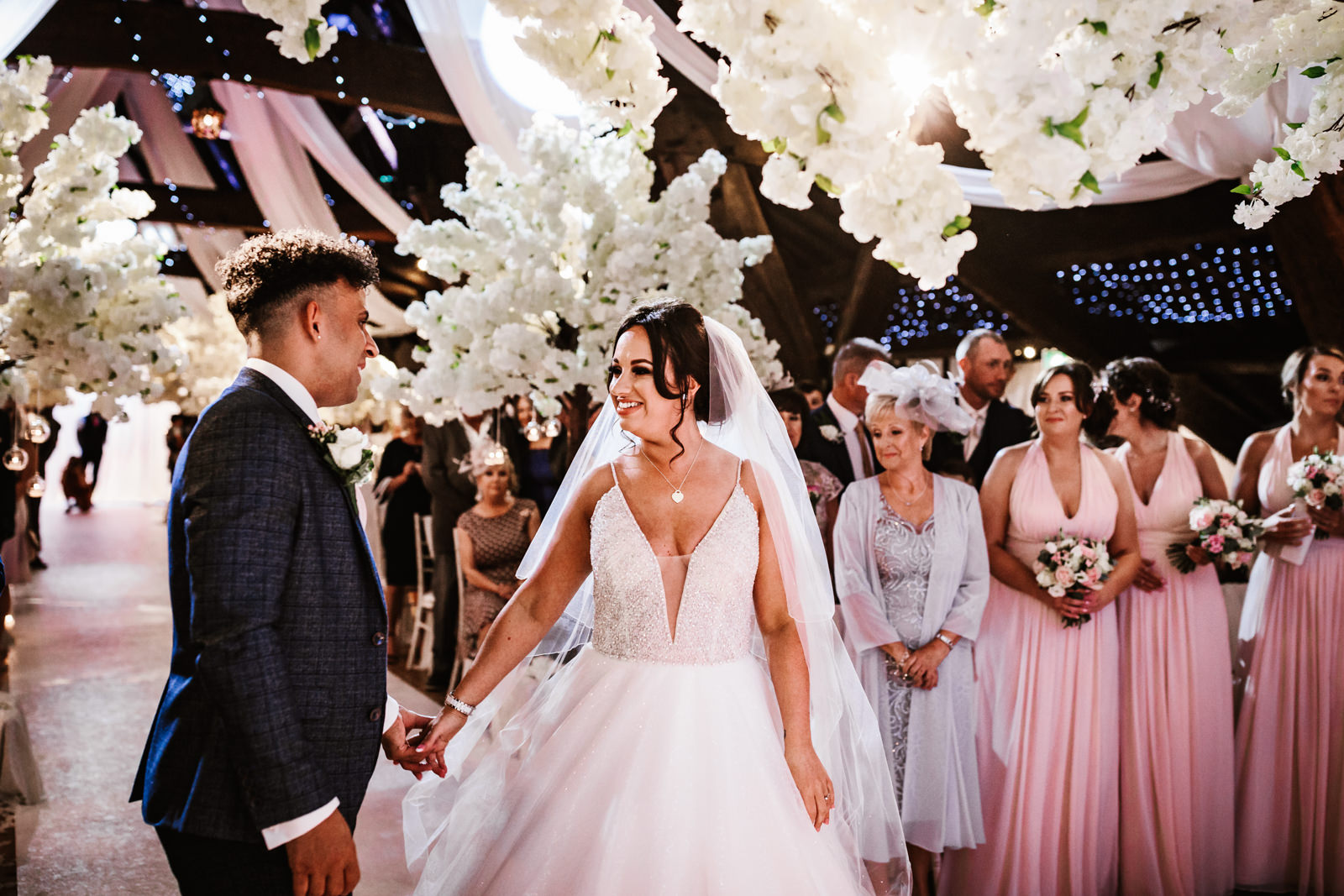 Bride and groom see each other for the first time at the end of the aisle