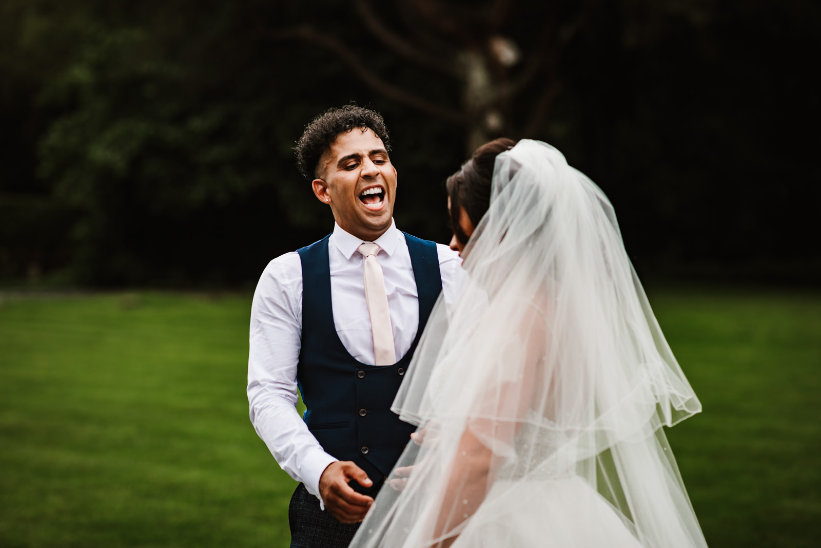 Groom laughing with his wife