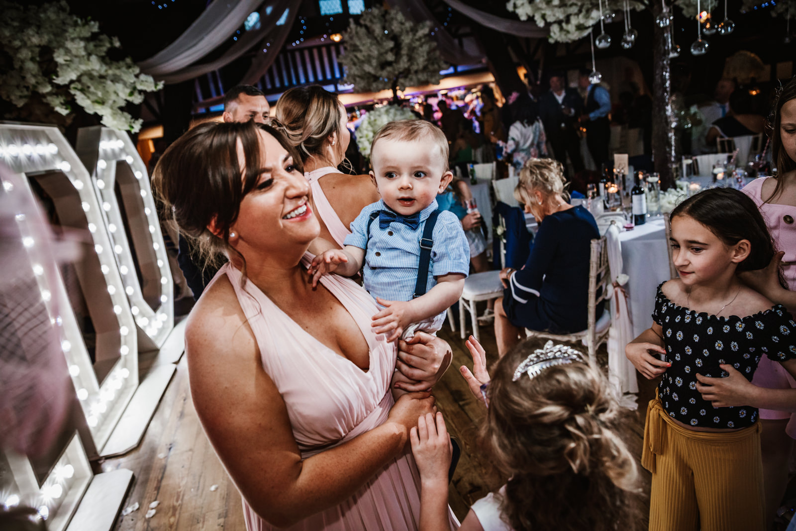 Bridesmaid holding little boy on dance floor
