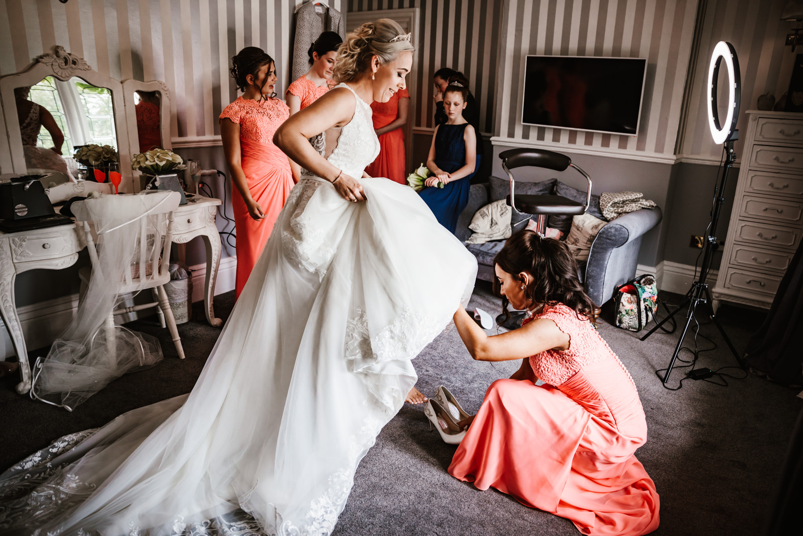 Bride getting help with her wedding shoes