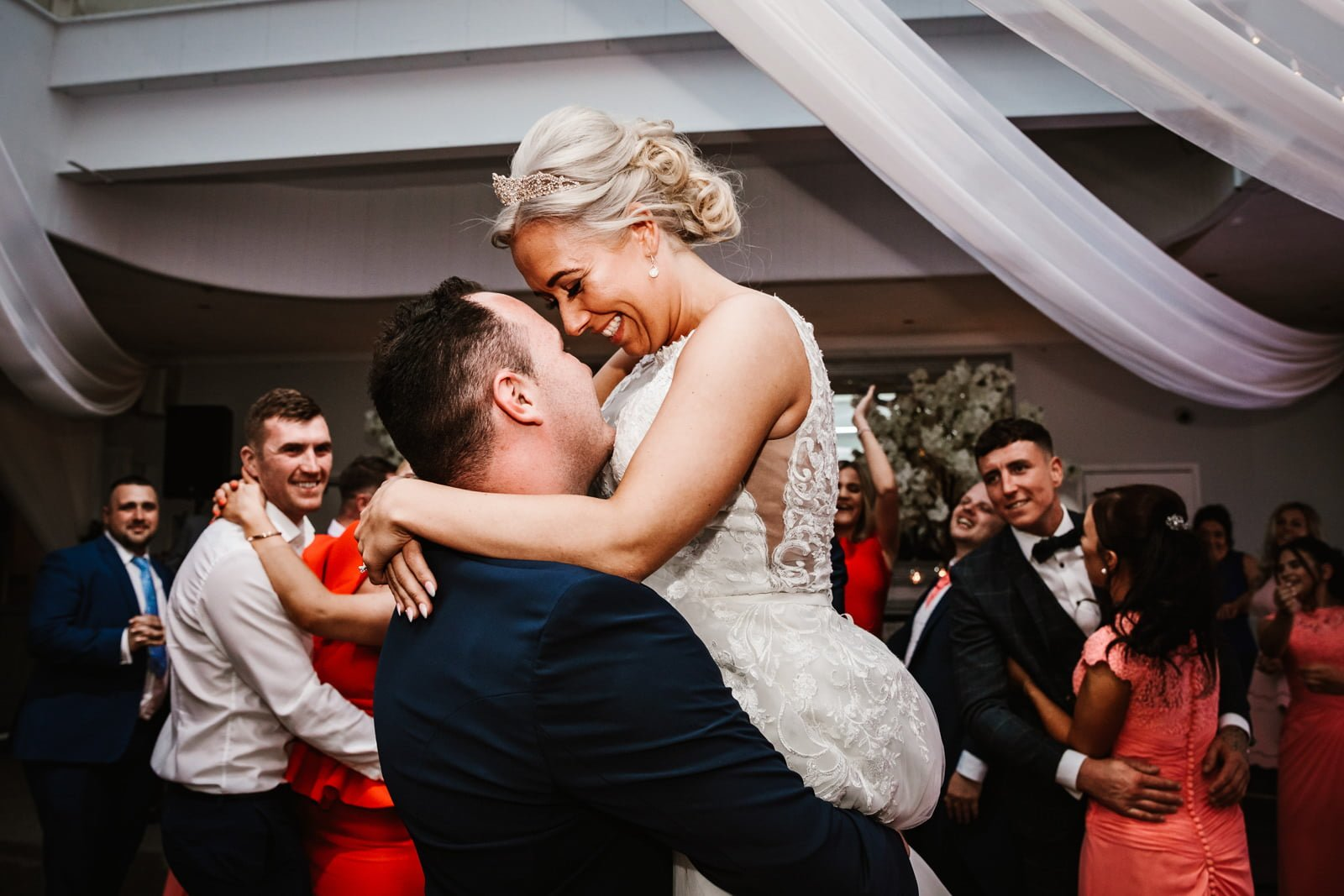 Groom picks up his bride during first dance