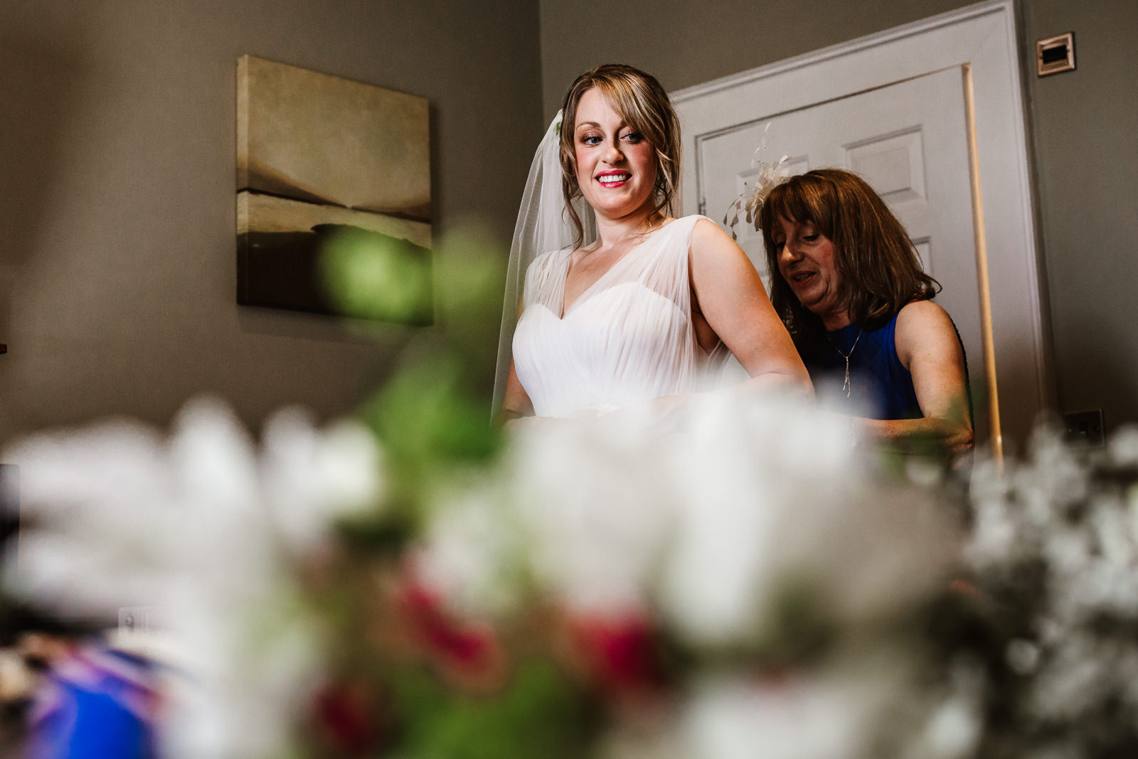 Brides mother elping her into her dress
