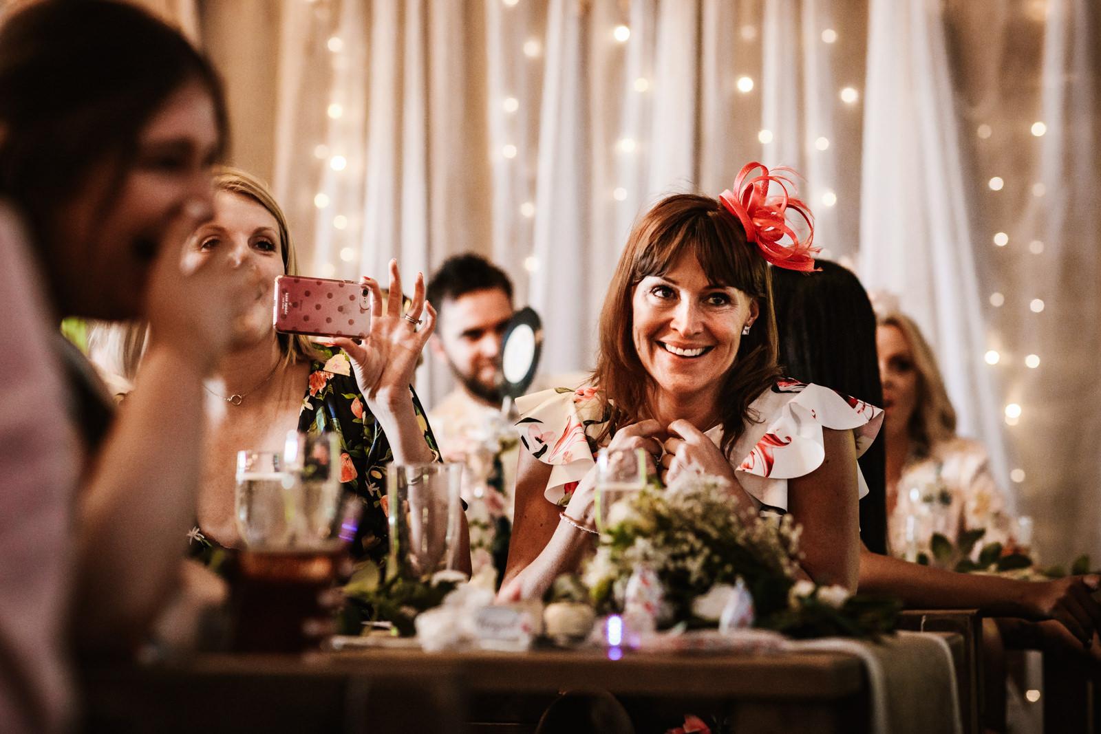 Wedding guest smiling during best man speech