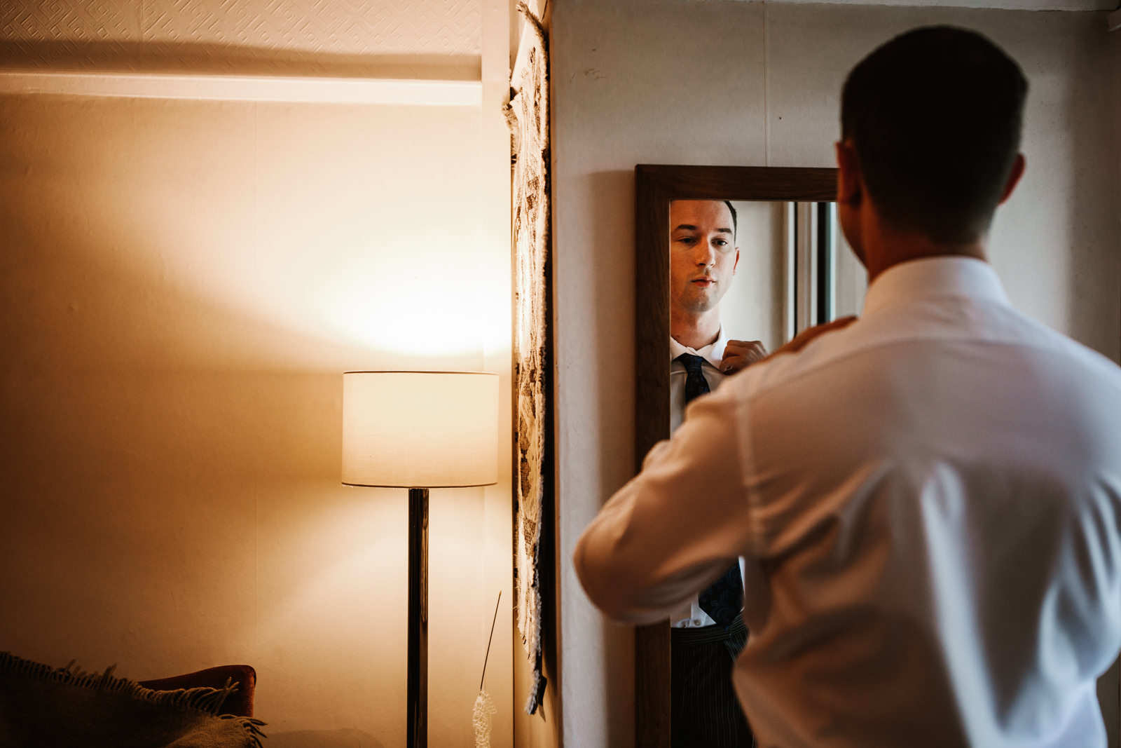 Groom getting ready in the mirror