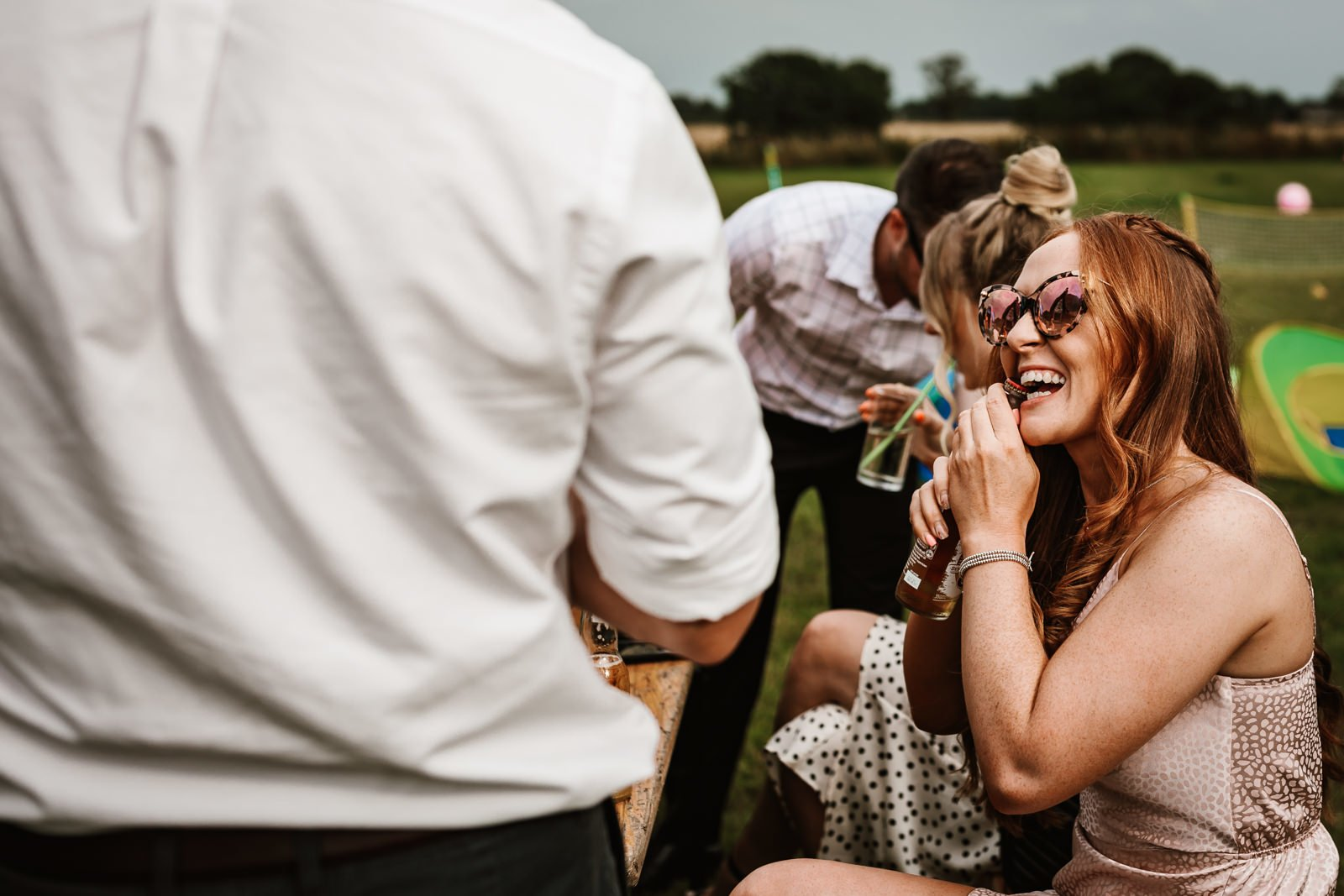 Wedding guest taking off bottle top with her teeth