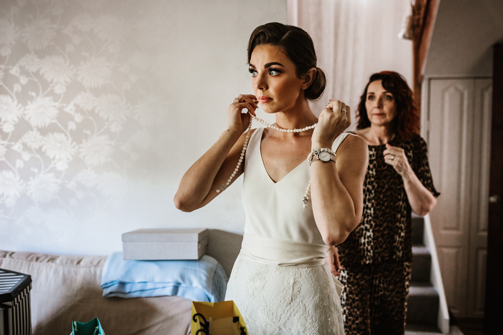 Bride putting on a pearl necklace