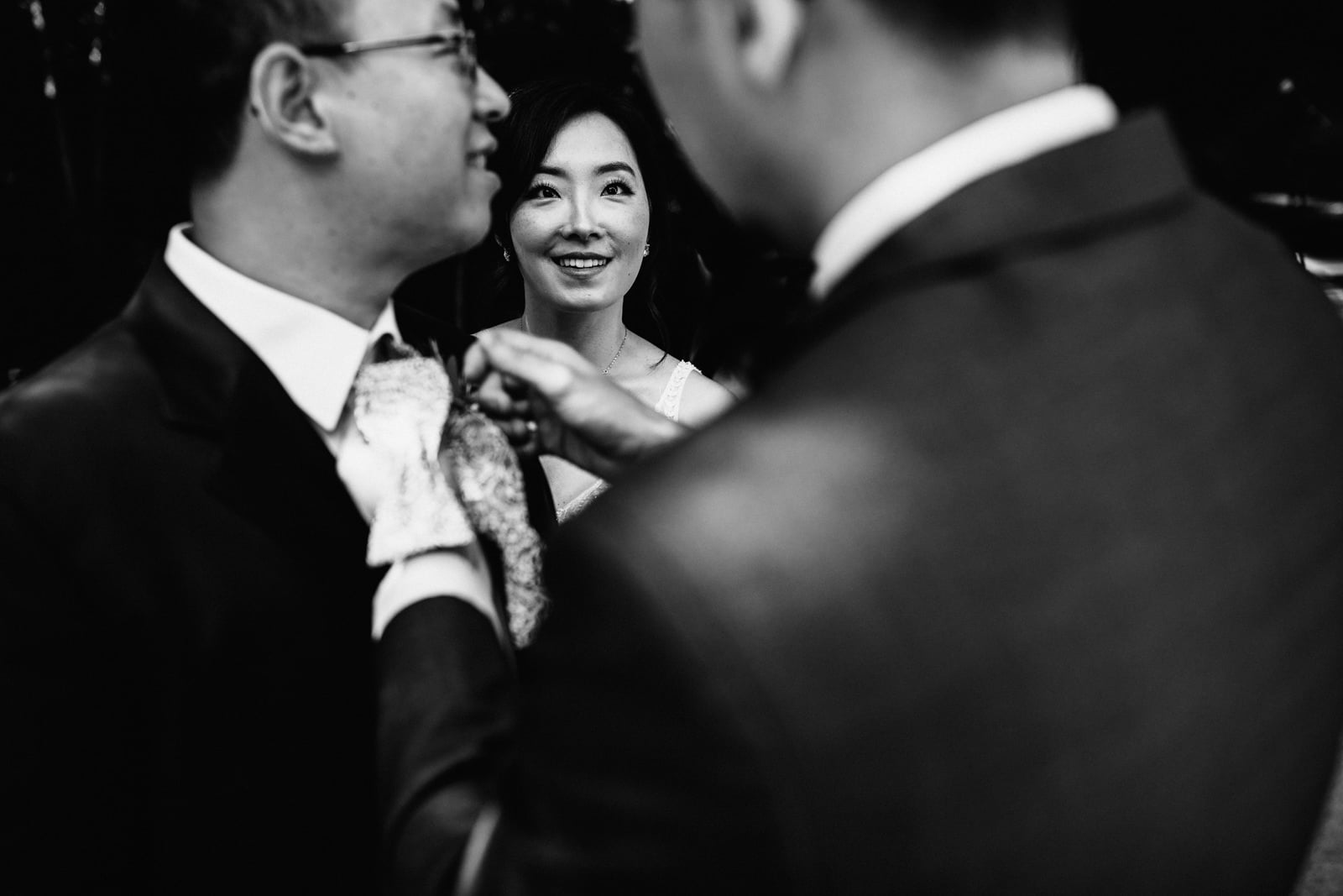 Bride watching her husband to be having his tie fixed