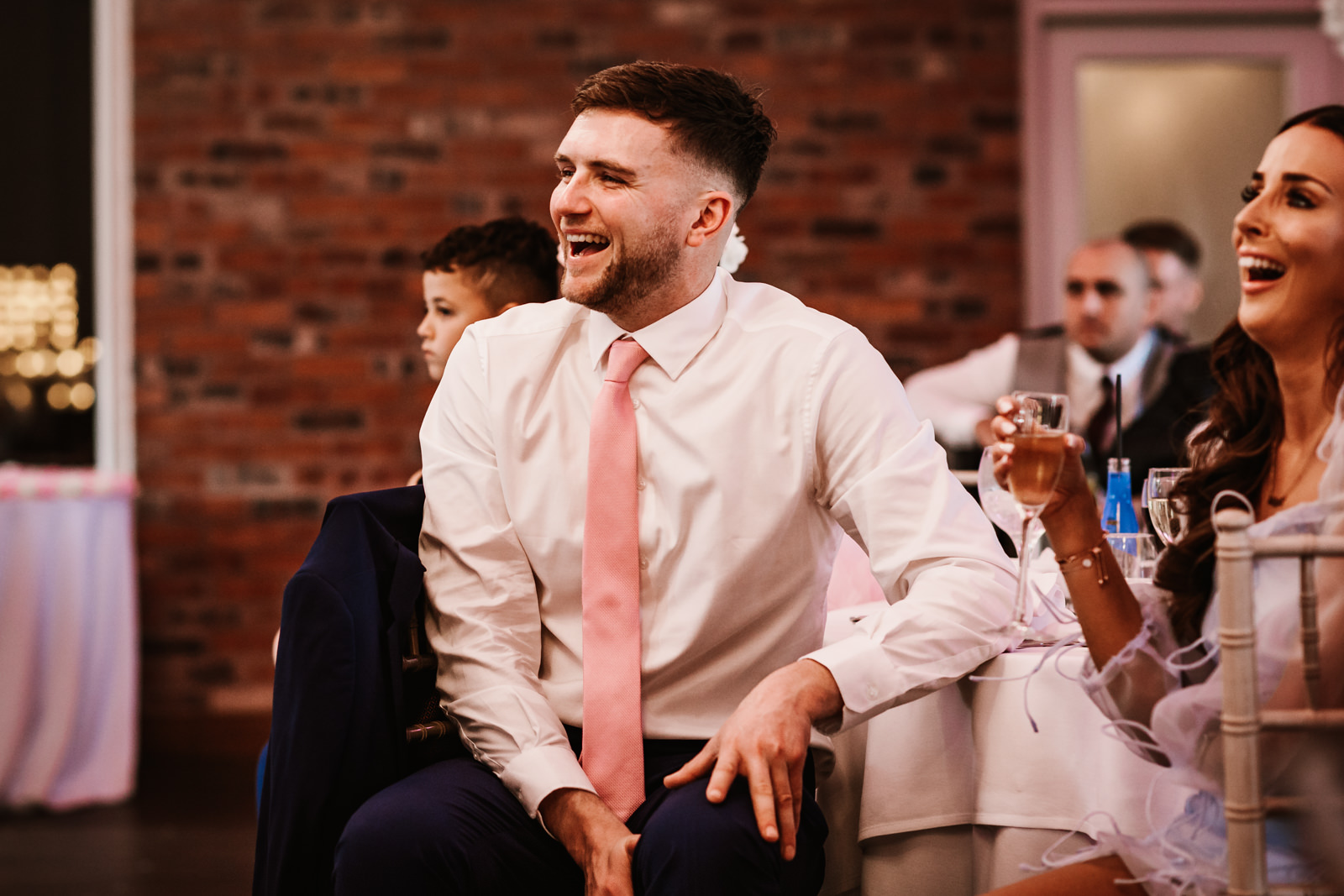 Brother of the bride laughing during speeches