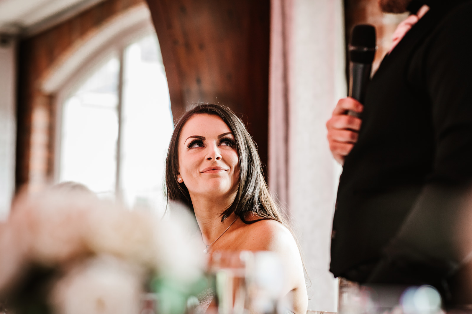 Bride looking at her husband during his speech