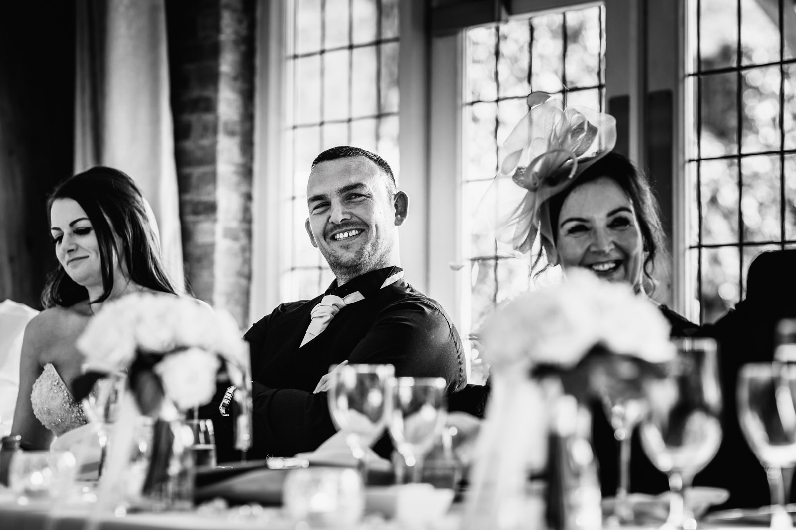 The groom laughing during his best mans speech